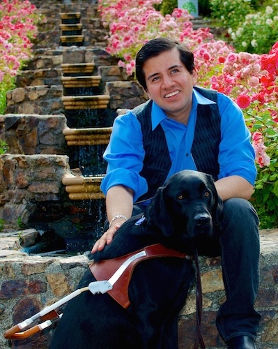 A picture of Oleb Media founder Belo Cipriani, wearing a blue collared shirt and a black vest, sitting in a colorful garden with his guide dog, Oslo.
